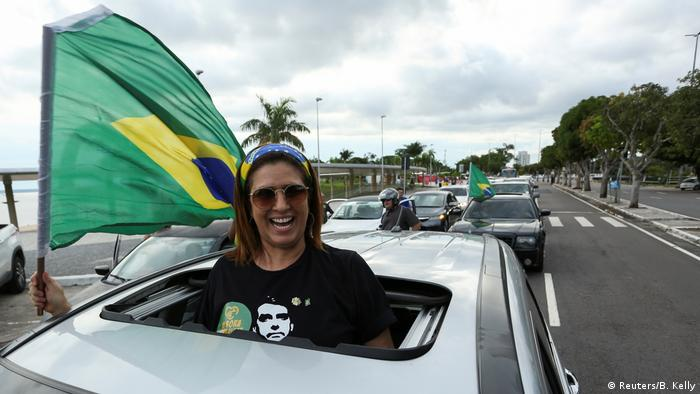 A supporter of Jair Bolsonaro waves a Brazilian flag from a motorcade in Manaus