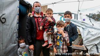 Семья беженцев в самодельных защитных масках на острове Лесбос