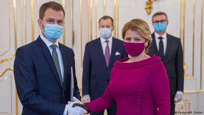 Zuzana Čaputová com máscara da cor do blusão apertando a mão de Igor Matovic, com máscara e terno