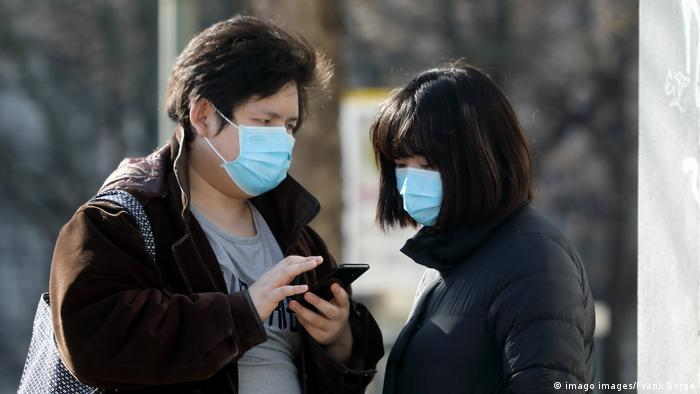 Two people wearing face masks look at a smartphone