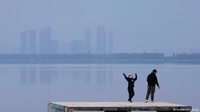 A woman in face mask dances on East Lake in Wuhan standing next to a man