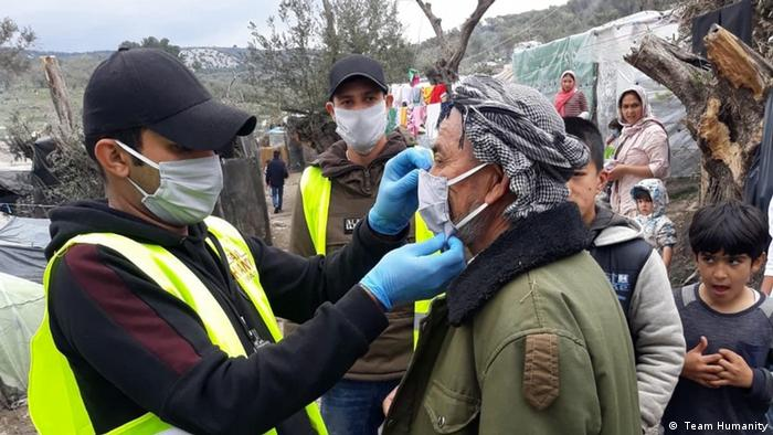 An aid worker fits a person with a face mask at the Moria refugee camp