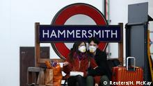 A couple wearing protective face mask's at Hammersmith underground station as the spread of the coronavirus disease (COVID-19) continues, London, Britain, March 24, 2020. REUTERS/Hannah McKay