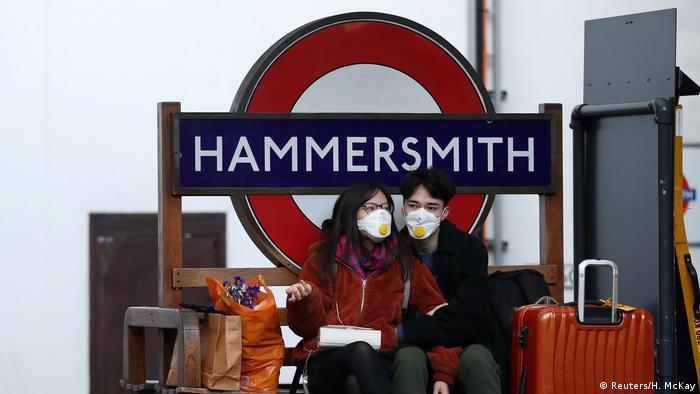 Una pareja con mascarillas en la estación londinense de metro Hammersmith