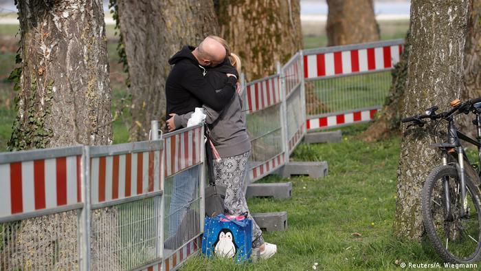 Couple hugging each other across a border barrier, Kreuzlingen on Lake Constance, German-Swiss border (Reuters/A. Wiegmann)