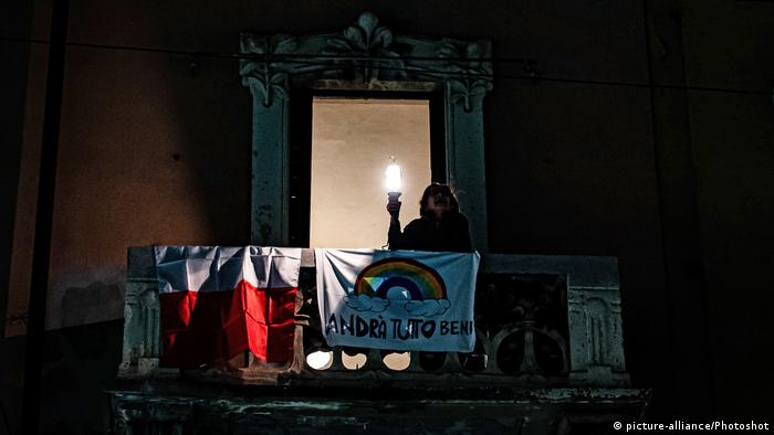 A woman in Milan holds a torch from her balcony drapped with a flag that reads Everythign will be fine in Italian