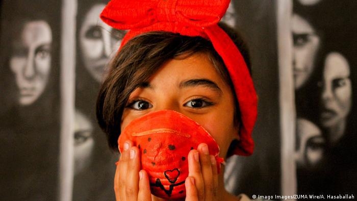 Foto de una niña palestina con una mascarilla roja