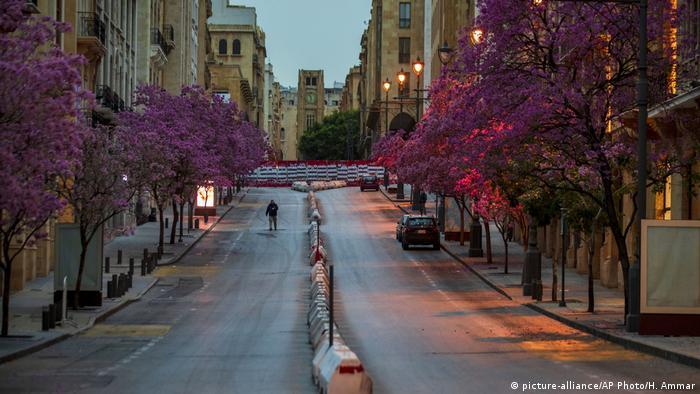 A lone man walks down a Beirut boulevard