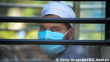 A man wearing a protective facemasks looks out while sitting on a special service bus taking them to a quarantine facility amid concerns about the spread of the COVID-19 coronavirus in Nizamuddin area of New Delhi on March 31, 2020. (Photo by Sajjad HUSSAIN / AFP) (Photo by SAJJAD HUSSAIN/AFP via Getty Images)