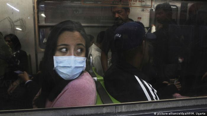 A woman wearing a mask rides in the Mexico City's subway