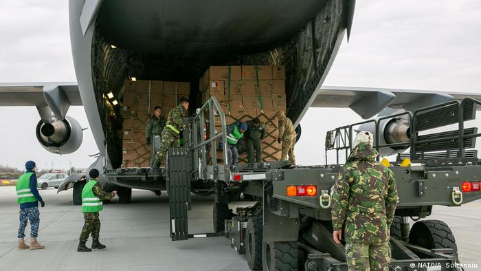 The Romanian military unloads emergency assistance it purchased from South Korea and shipped with C-130s it shares in a NATO program.