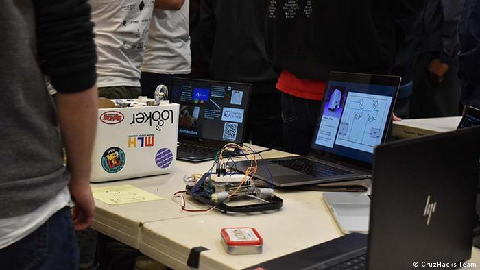 Electronic devices and designs on laptops laid out at hackathon in Santa Cruz