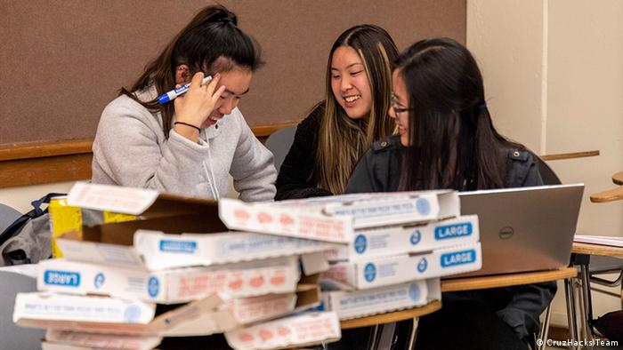 A group of three female students sit behind pizza boxes at CruzHacks