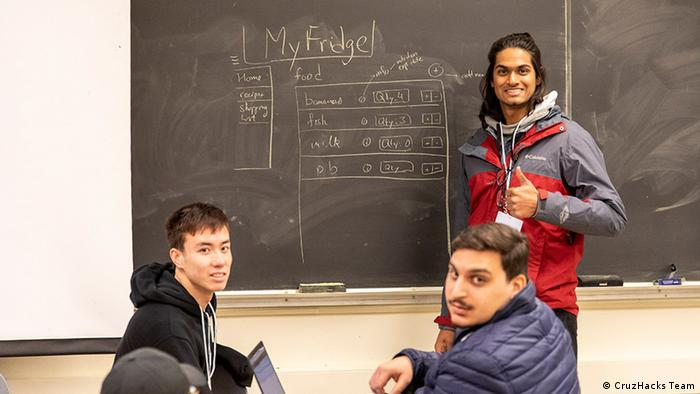 A team of three members stands in front of a black board at CruzHacks