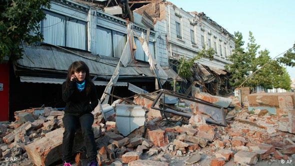Eine Frau sitzt auf Trümmern in der Stadt Talca, Chile (Foto: AP)