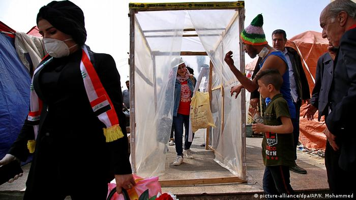 Protesters walk through a makeshift disinfection cabin on Tahrir Square in Iraq