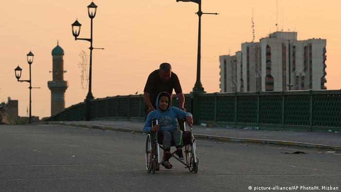 A man pushing a boy in a wheelchair cross an empty bridge over the Tigris River in Baghdad
