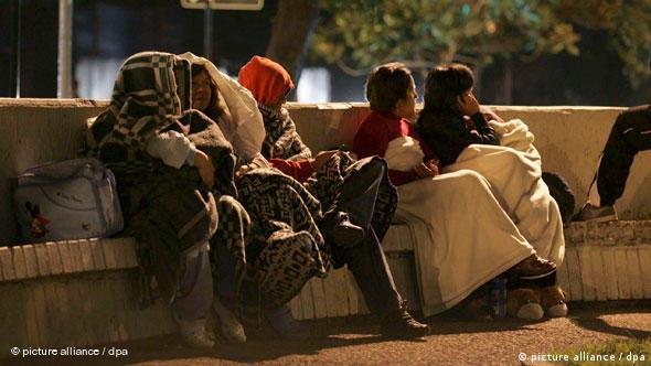 Menschen verbringen in Decken gehüllt die Nacht auf einer Bank Santiago de Chile (Foto: dpa)