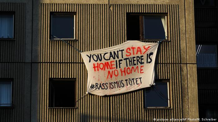 A poster supporting homeless people and refugees is displayed at an apartment building in central Berlin