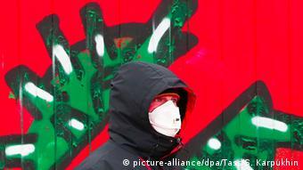 Человек в маске на фоне рисунка на стене, изображающего коронавирус