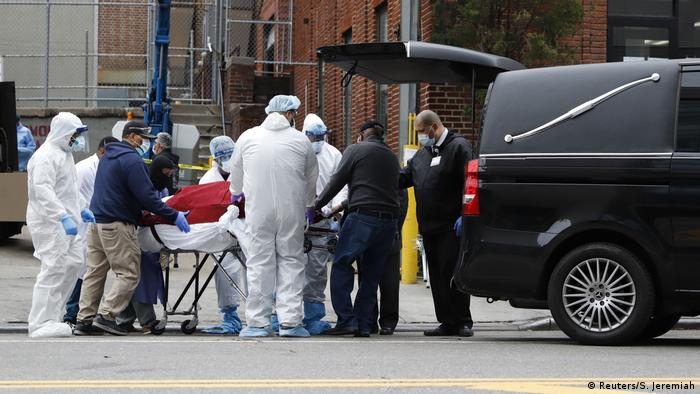 Workers load the body of a deceased person into a waiting hearse vehicle outside The Brooklyn Hospital Center
