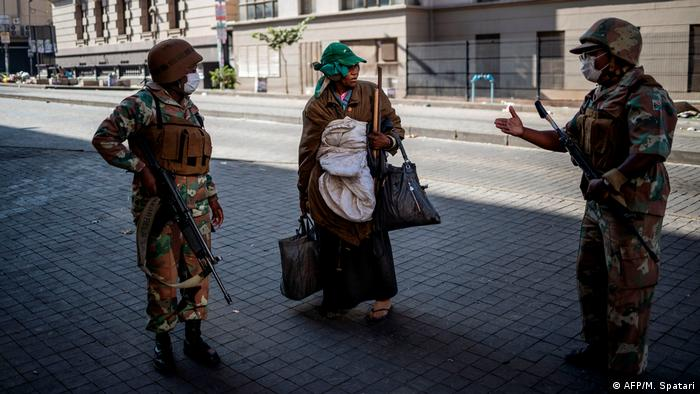 South African police speak with a homeless woman during the coronavirus lockdown (AFP/M. Spatari)