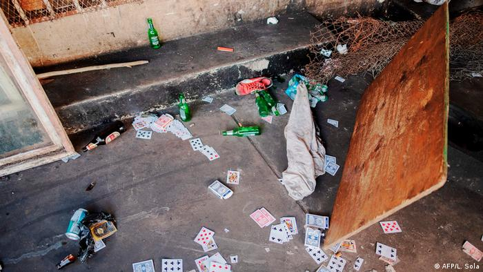 Beer bottles and playing cards scattered on the ground (AFP/L. Sola)