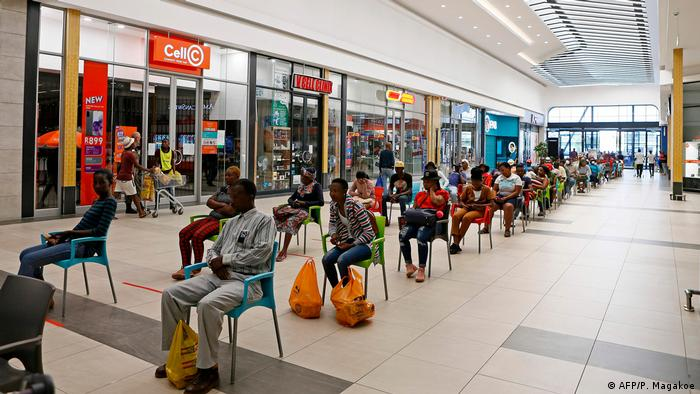 People on chairs in a shopping center (AFP/P. Magakoe)