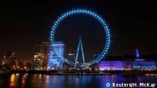 England London | Das London Eye Riesenrad leuchtet Blau als Zeichen der Solidarität mit der NHS