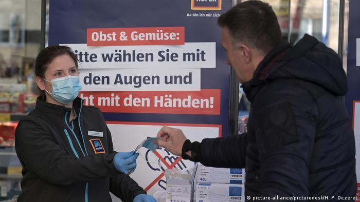 Funcionários de supermercados distribuem máscaras na Áustria