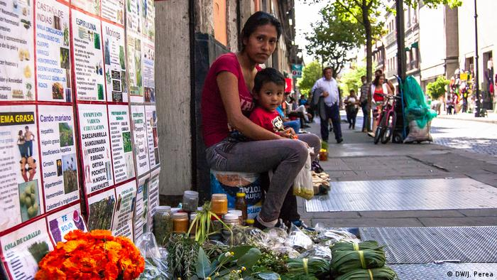 A woman with her child sitting next to their street stand in Mexico City