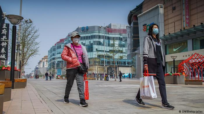 Women wearing masks for protection against COVID-19 walk on Wangfujing shopping street in Beijing, China