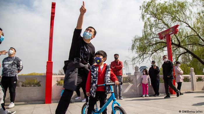A man wearing a mask for protection against COVID-19 points at a kite in Taoranting Park in Beijing, China
