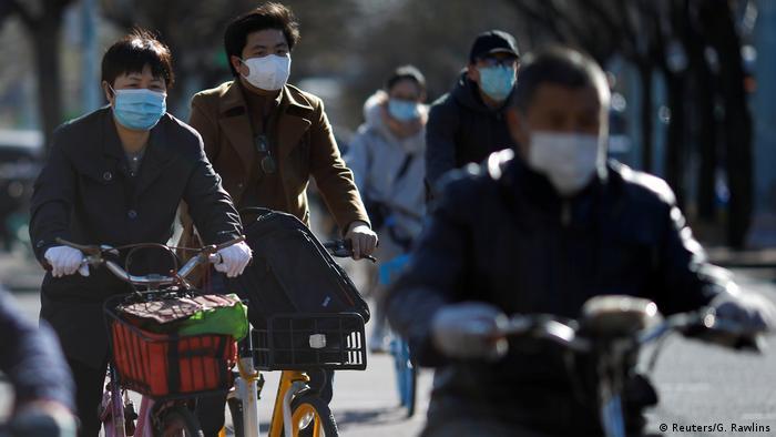 People wearing face masks ride bikes in Beijing