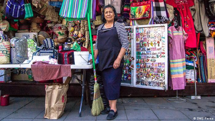A street vendor in Mexico City standing in front of her stand with artisan goods