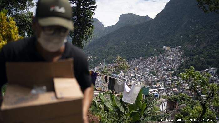 Voluntário carrega caixa com sabão e detergente para ser distribuída na Rocinha, no Rio