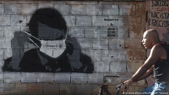 A graffiti of Jair Bolsonaro adjusting a face mask in Rio de Janeiro