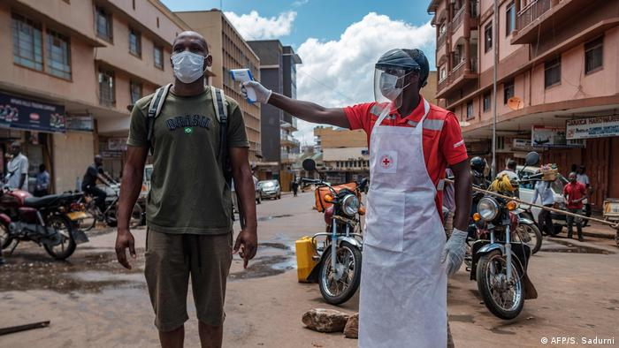 A man checks the temperature of another in the streets of Kampala.