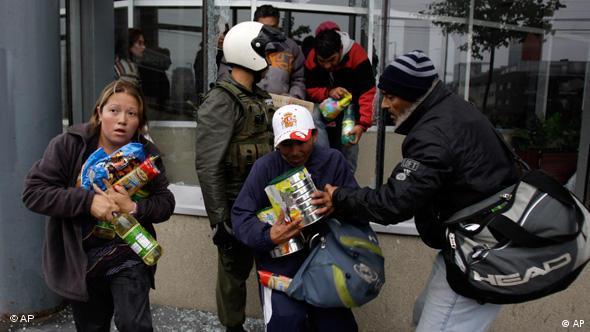 Menschen rennen mit geklauten Lebensmitteln davon, Conception, Chile nach dem Erdbeben (Foto: AP)