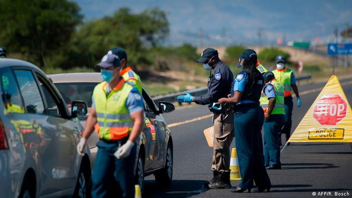 Police man a checkpoint in Cape Town erected as part of coronavirus measures