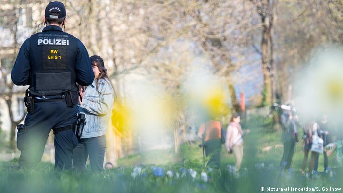 صورة من الأرشيف لشرطي يتحدث مع مواطنة حول فيروس كورونا في إحدى حدائق شتوتغار