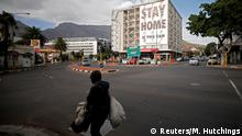 FILE PHOTO: A man walks past a poster covering the side of a building ahead of a 21 day lockdown aimed at limiting the spread of coronavirus disease (COVID-19), in Cape Town, South Africa, March 26, 2020. REUTERS/Mike Hutchings/File Photo