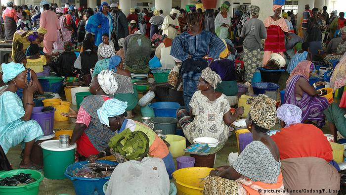 Women selling wares in a crowded market in Dakar, Senegal