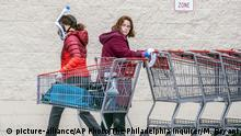 A Costco employee, right, looks towards a shopper wearing a mask and snorkel to go shopping, as she sanitizes carts that are returned from the parking lot to help reduce the spread of coronavirus, in King of Prussia, Pa., Wednesday, March 25, 2020. (Michael Bryant/The Philadelphia Inquirer via AP) |