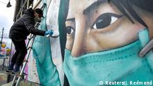 Street artist Carlos Giovanni, who goes by the name TheyDrift, works on the portrait of a healthcare worker for a piece he calls Stay Home on the same day that Governor Jay Inslee extended his stay-home order until May 4 as efforts continue to slow the spread of coronavirus disease (COVID-19) in Seattle, Washington, U.S. April 2, 2020. REUTERS/Jason Redmond