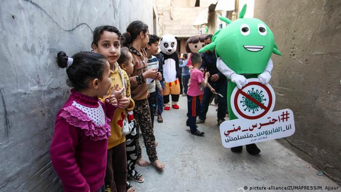 Palestinian clowns wearing anthropomorphs, one of them depicts the coronavirus, visit the children staying at homes as a preventive measure