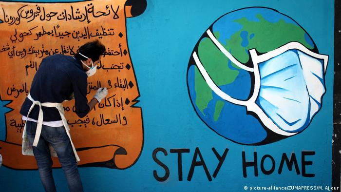 Palestinian artists draw a mural ''stay home'' during awareness campaign about the spread of coronavirus disease