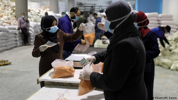 Workers pack food supplies to be distributed and delivered by the United Nations Relief and Works Agency