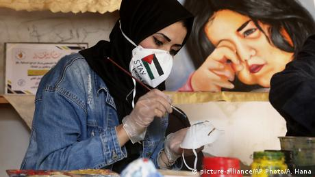Palestinian artist Samah Saed decorates a protective face mask