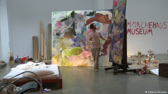 Alexander Iskin stands in front of painted canvasses next to a bed (Galerie Sexauer)
